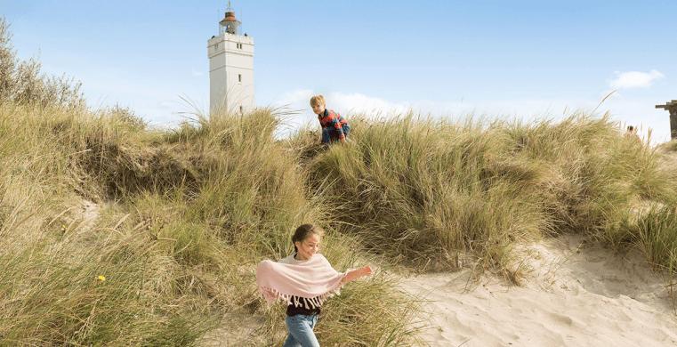 Børn leger i klitterne på deres sommerhustur i Blåvand.