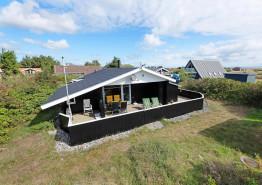 Hus med lukket terrasse og brændeovn og trælaminatgulv