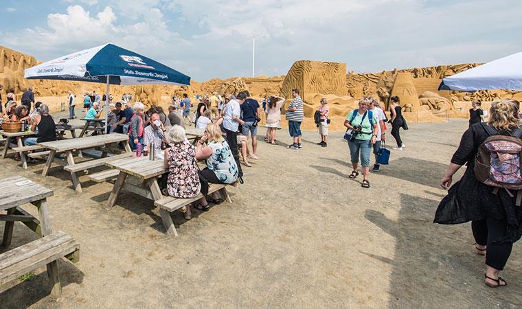 Besuche das Sandskulpturfestival und bring den picnickkorb-mit